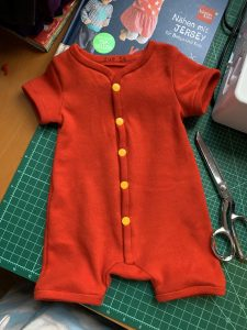 handmade red baby suit with yellow snaps